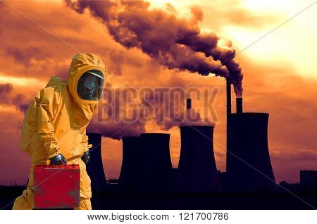 View of smoking coal power plant at sunset and men in protective hazmat suit