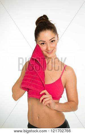 Isolated fitness woman wiping her cheek with a towel