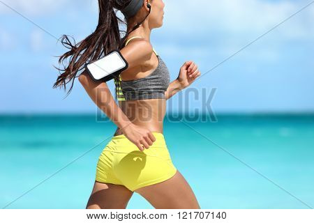 Sports phone armband fitness jogger exercising on beach - cardio workout. Midsection closeup of female athlete runner jogging wearing smartphone sleeve and earphones. Glutes training.