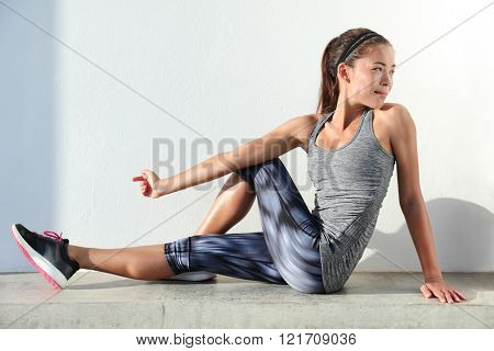 Fitness woman stretching legs doing pilates leg stretches exercises in outdoor gym. Asian athlete exercising abductor hip flexor muscle in buttocks to relieve sports pain.