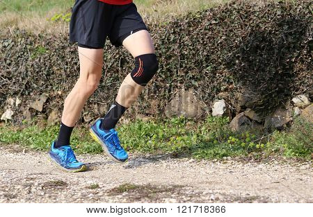 Cross-country Runner During The Race With His Knee Wrapped By A Knee Brace