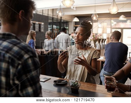 Beautiful African woman talking and using her hands to describe her business proposal, at a meeting in a busy and modern coffee shop