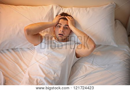 Young man lying in bed at home