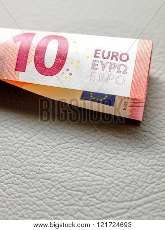 Ten Euro paper currency wraped in tubular shape on leather seats of a sport car