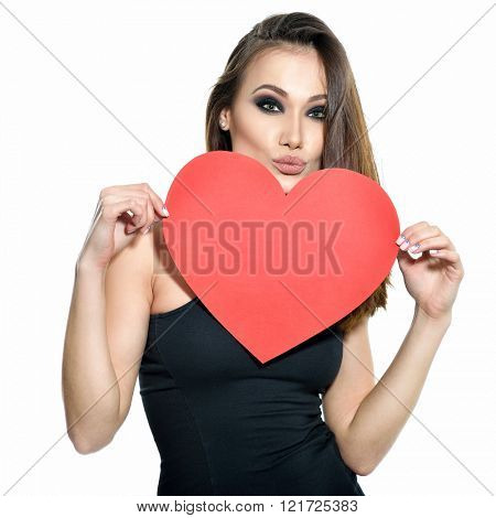 Heartbreaker. Temptress. Seductive woman. Portrait of amazing young fashion woman posing at studio with red heart. Love. Valentine's day.