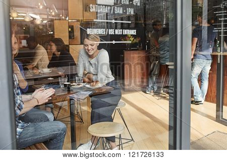 Young woman sitting at a high table in a busy modern cafe, smiling while enjoying coffee with frineds on a lunch break