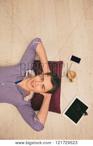 Top View Photo Of Man Lying On The Floor With Cup, Phone, Glasses And Tablet
