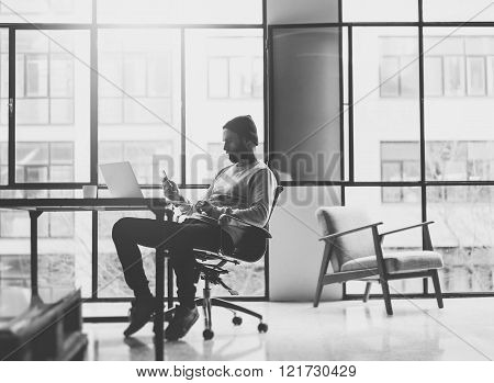 Bearded architect working on modern loft office. Texting message smartphone. Generic design notebook