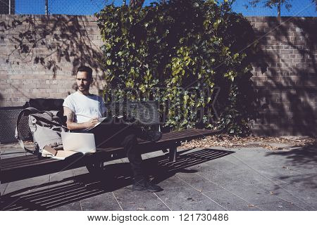 Man wearing white tshirt sitting city park and reading book. Studying at the University, preparation