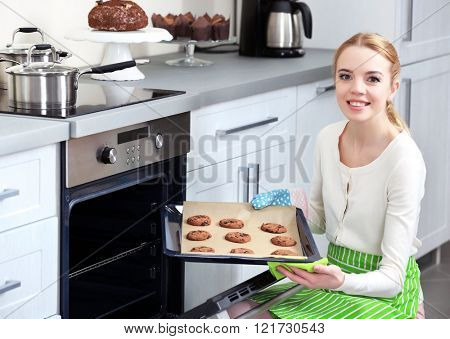 Young woman removing cookie tray from the oven in a kitchen