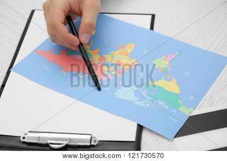 Male hand with pen and world map on the table