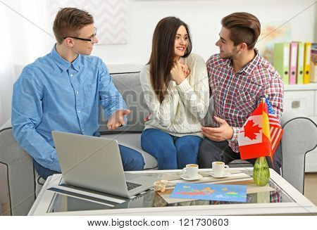 Agent offering vacation options for happy young couple in the office of travel company