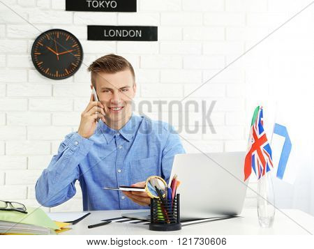 Young man talking on the smart phone and showing passports with tickets in the office of travel company