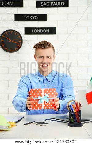 Young man showing gift box in the office of travel company