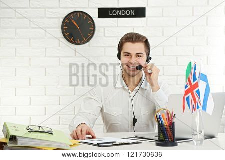 Young man talking on headset in the office of travel company