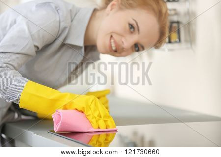 Young woman scrubbing the electric stove with a rag