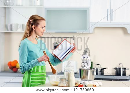 Young woman using a notebook to follow a recipe