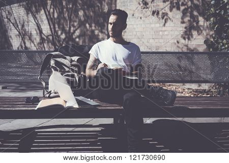 Photo man wearing white tshirt sitting city park and writing message book. Studying at the Universit
