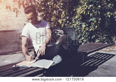 Student wearing white tshirt sitting city park bench and writing textbook message. Studying at the U
