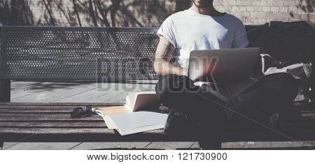 Photo man sitting city park and texting message notebook. Studying at the University, working projec