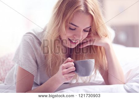 Attractive young blonde girl in a pajama holding a cup while laying in bed