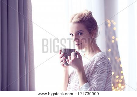 Blonde beautiful  girl looking in the window and holding a cup of coffee or tea in her hands