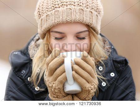 Beautiful girl enjoying a cup of tea outdoors