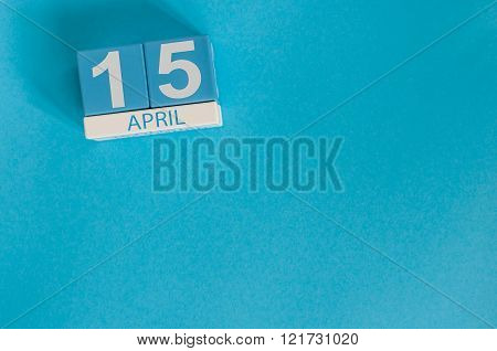 April 15th. Tax Day. Image of april 15 wooden color calendar on blue background.  Spring day, empty