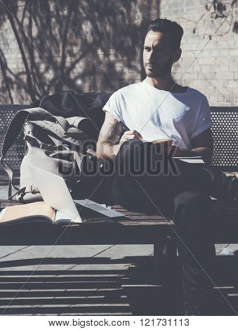 Photo bearded man wearing white tshirt sitting city park and draws notepad. Studying at the Universi