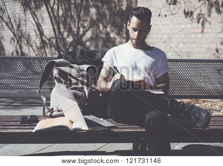 Photo bearded artist wearing white tshirt sitting city park and draws. Studying at the University, w