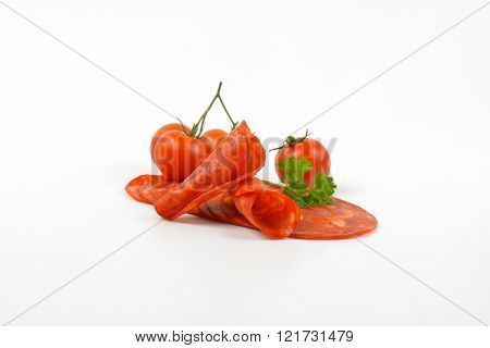 slices of chorizo salami with parsley and cherry tomatoes on white background