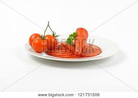 plate of chorizo salami and cherry tomatoes on white background