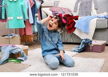 Little girl in the room with a lot of clothes
