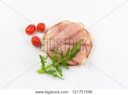 stack of ham slices with fresh dill and cherry tomatoes on white background