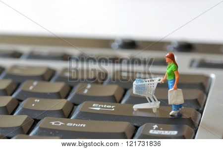 Miniature shopper with shopping cart on a computer keyboard