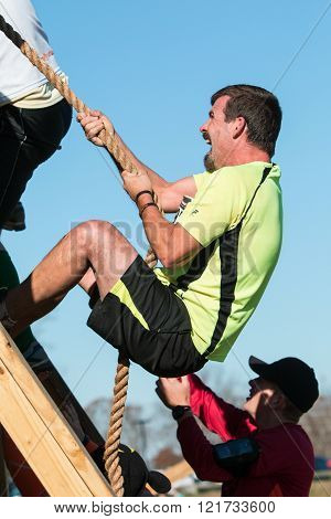 BUFORD, GA - NOVEMBER 2015:  A man struggles to use a rope to climb up a wall at one of the obstacles at the Muddy Brute Challenge in Buford, GA on November 21, 2015.