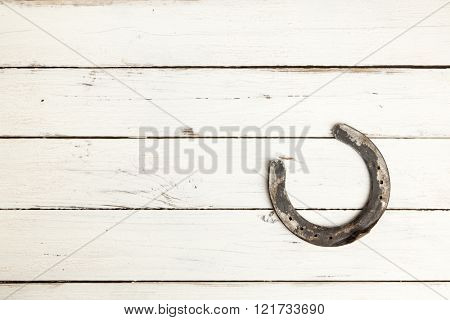 old horseshoe with copy space on white painted planks
