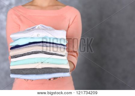 Woman hold clothes pile against grey background, close up