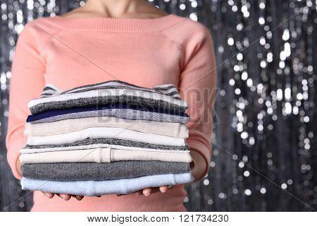 Woman hold clothes pile against silver shining background, close up
