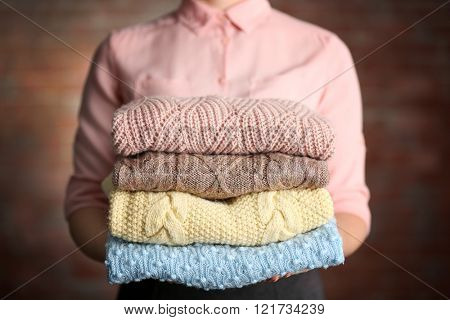 Stack of knitted clothes in female hands on blurred wall background