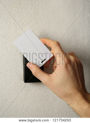 Security alarm with male hand on wall background, closeup