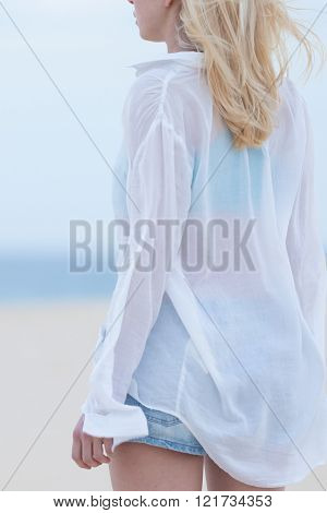 Woman on sandy beach in white shirt at dusk.