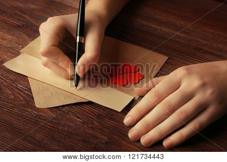 Female hands signing gift card for Valentine's Day on wooden background