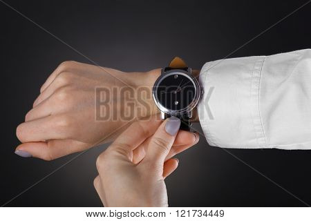 Modern watch on a woman's wrist over black background