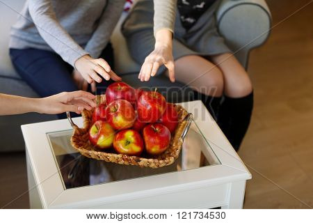 Female hands taking apples from the basket