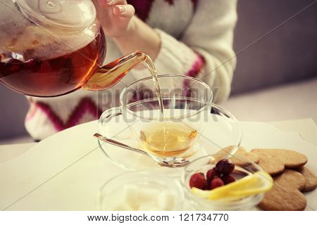 Woman pouring tea into the cup