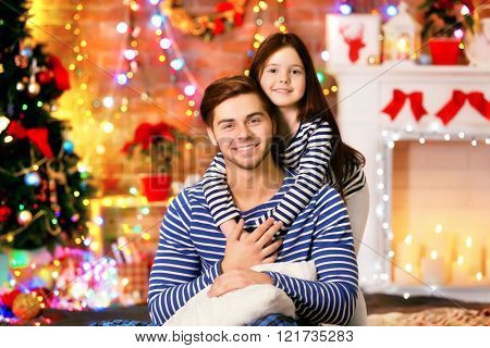 Older brother with little sister embracing in Christmas living room