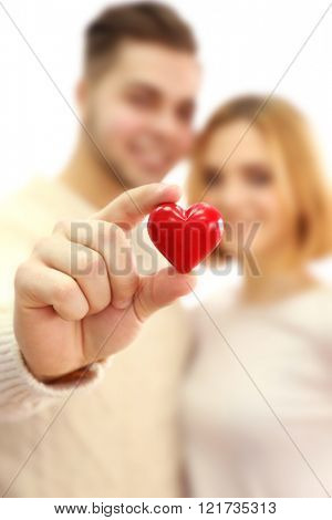 Young couple in love holding red heart, close up