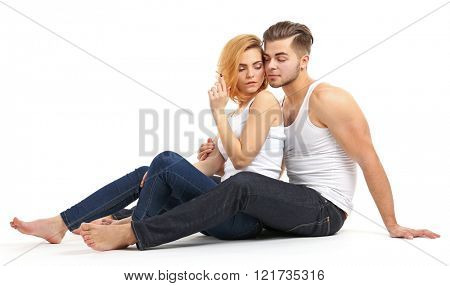 Young couple in love sitting together, isolated on white