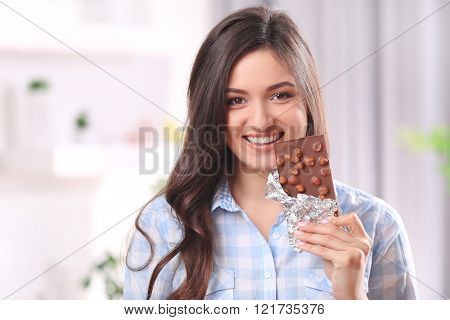 Portrait of beautiful young brunette with chocolate in the room , close up